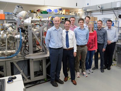 A group of Scienta Omicron and School of Chemistry, University of Bristol researchers standing with the NanoESCA System.  | © University of Bristol